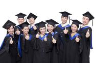 Portrait of graduates showing thumbs up Stock Photos