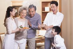 Happy family appreciating young woman's cooking - stock photo