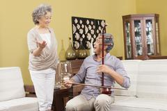 Senior couple playing Chinese traditional musical instrument Erhu Stock Photos