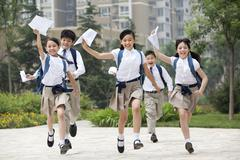 Cheerful schoolchildren in uniform with results lists in hands Stock Photos