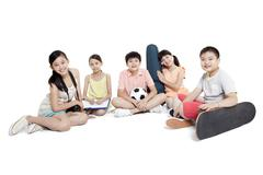 Merry children sitting on the floor and their leisure hobbies - stock photo