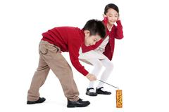 Little boy and little girl igniting firecracker together - stock photo