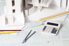 Architectural model with other office stationery on blueprints Stock Photos