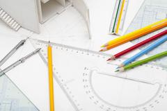 Office stationery and building model in design studio Stock Photos