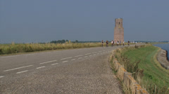 Cyclists passing Plompe Toren, a medieval tower at a dike Eastern Scheldt Stock Footage