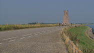 Stock Video Footage of Cyclists passing Plompe Toren, a medieval tower at a dike Eastern Scheldt