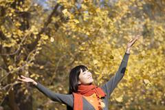 Happy young woman appreciating the golden autumn - stock photo