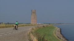 Cyclists at a dike passing Plompe Toren, a medieval tower + pan Eastern Scheldt Stock Footage