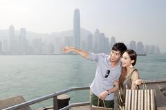 Happy young couple with shopping bags appreciating the spectacular view of - stock photo