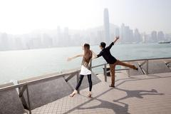 Happy young couple appreciating the spectacular view of Victoria Harbor, Hong - stock photo