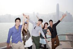 Cheerful young friends appreciating the spectacular view of Victoria Harbor, - stock photo