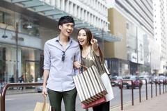 Cheerful young couple with shopping bags hanging out in the street, Hong Kong Stock Photos