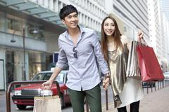 Cheerful young couple with shopping bags walking in the street, Hong Kong - stock photo