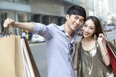 Cheerful young couple with shopping bags hanging out in the street, Hong Kong - stock photo