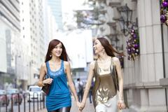 Cheerful best female friends go shopping in Hong Kong - stock photo