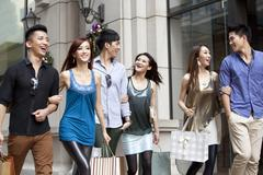 Excited young people go shopping on the street of Hong Kong Stock Photos
