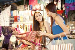 Fashionable young women shopping on Temple Street of Hong Kong, night view - stock photo