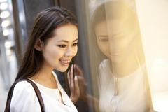 Beautiful young woman doing window shopping in Hong Kong - stock photo