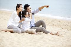 Happy young family appreciating the view with binoculars on the beach of Repulse - stock photo