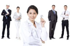 Professional female doctor with different occupation workers in background - stock photo