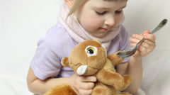Little girl giving syrup to her plush toy Stock Footage