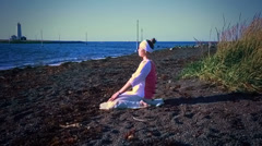 Woman meditating on a calm Icelandic beach Stock Footage