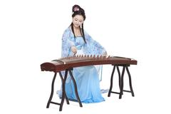 Young woman in Chinese traditional costume plucking Chinese zither Stock Photos
