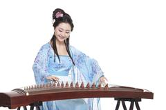 Young woman in Chinese traditional costume plucking Chinese zither - stock photo