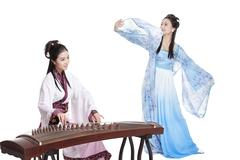 Young women in Chinese traditional costume plucking Chinese zither and dancing Stock Photos