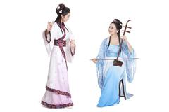 Young women in Chinese traditional costume plucking Erhu and dancing - stock photo