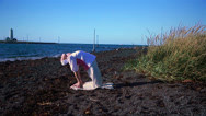 Stock Video Footage of Woman doing yoga poses on a calm Icelandic beach, ankle stretch