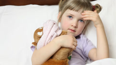 Little girl touching her forehead and forehead her plush toy Stock Footage