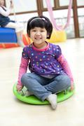Cute girl sitting on a big toy dreidel in kindergarten - stock photo