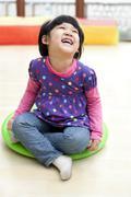 Laughing girl on a big toy dreidel in kindergarten - stock photo