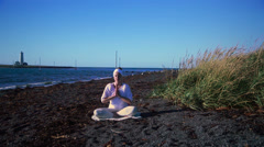Woman meditating in summer on a calm Icelandic beach, prayer position - stock footage