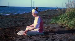 Woman doing yoga poses on a calm Icelandic beach 7 - stock footage