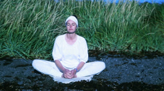 Woman meditating in summer on a calm Icelandic beach cool  - stock footage