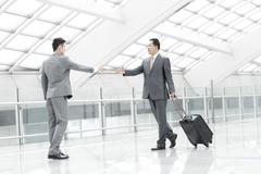 Business partners meeting in airport lobby Stock Photos