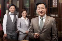 Successful businessman with team in background Stock Photos