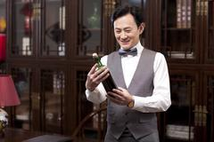Wealthy businessman with red wine bottle - stock photo