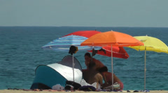 Hot beach day under brightly Colored Beach Umbrellas Stock Footage