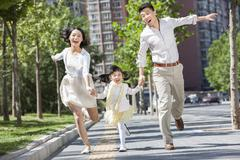 Excited young parents with daughter running on sidewalk hand in hand Stock Photos