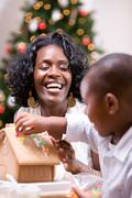 christmas: mother and son build holiday gingerbread house - stock photo