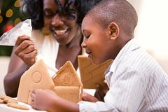 Christmas: mother and son build holiday gingerbread house Stock Photos