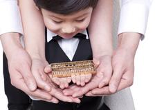 Family holding hands with abacus Stock Photos