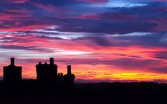 beautiful sunset with house chimneys silouette - stock photo