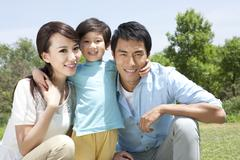 Happy Chinese family in a park Stock Photos