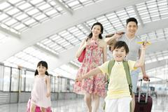 Happy family with luggage at the airport Stock Photos