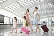 Stock Photo of Happy young family leaving with luggage