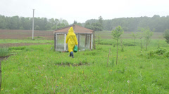 Woman in waterproof coat with watering-can to garden greenhouse Stock Footage